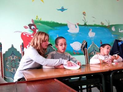 Una volontaria del progetto di logopedia al lavoro con due bambini in Marocco