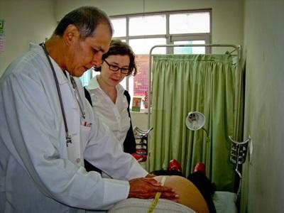Una volontaria osserva un dottore esperto all'opera in Bolivia