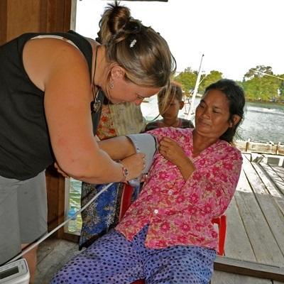 Una volontaria osserva un dottore esperto all'opera in Cambogia