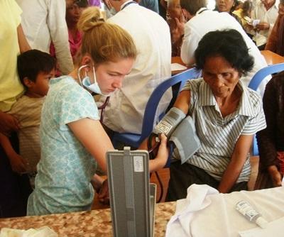 Una volontaria del progetto di medicina si prende cura di un paziente in Cambogia