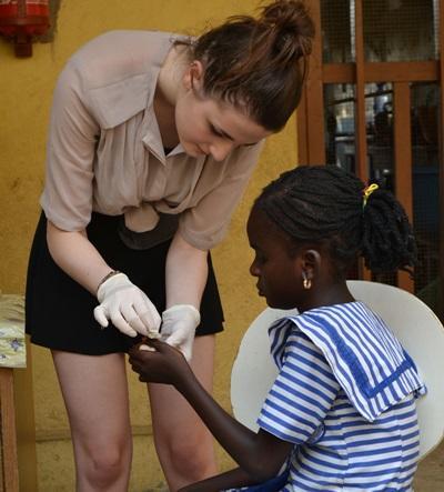 Ghana, una volontaria medica una paziente durante uno stage in medicina