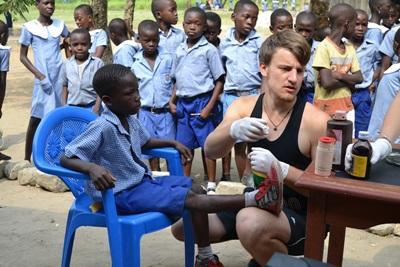 Un volontario cura un bambino durante una visita nei villaggi in Ghana