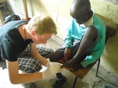 Kenya, un volontario si occupa di un piccolo paziente durante uno stage in medicina
