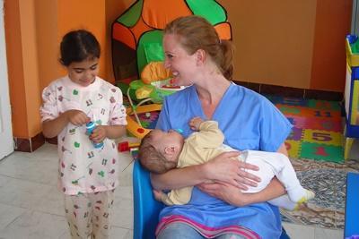 Una volontaria del progetto di medicina in Romania con due giovani pazienti