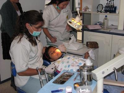 Una volontaria prepara una bambina a ricevere cure dentistiche in Bolivia