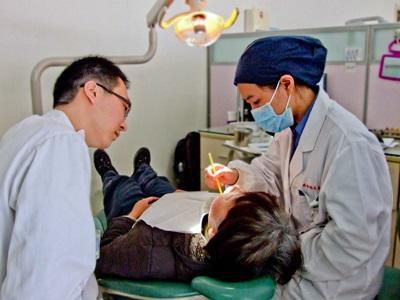 Cina, una volontaria assiste una dentista per il progetto di odontoiatria