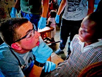 Un volontario visita una bambina per il progetto di odontoiatria in Kenia