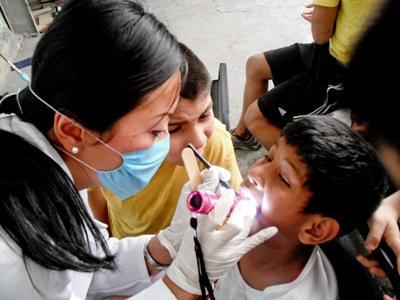 Una volontaria del progetto di odontoiatria cura un piccolo paziente in Messico