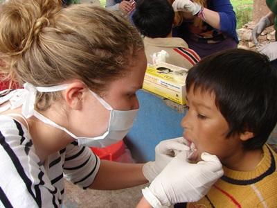 Una volontaria del progetto di odontoiatria visita un giovane paziente