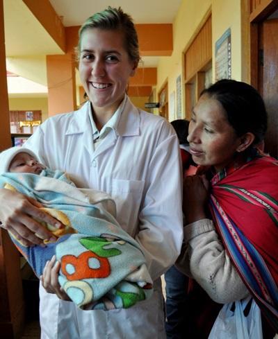 Una volontaria presta le prime cure ad un neonato in Perù