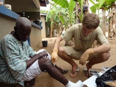 Un volontario cura le ferite di un paziente durante una visita nei villaggi