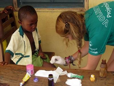 Una volontaria si prende cura di un bambino per il progetto di salute pubblica