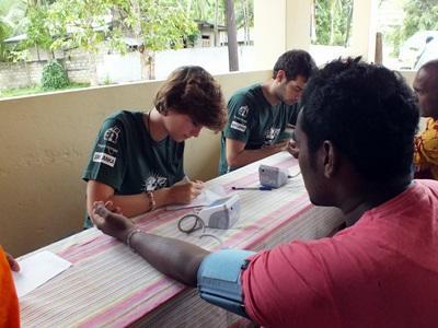 Un volontario di Projects Abroad controlla la pressione sanguigna durante una campagna