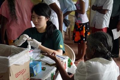 Una volontaria di Projects Abroad controlla il livello degli zuccheri nel sangue di una donna a Colombo