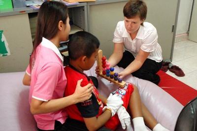 Alcune volontarie assistono un bambino in Cambogia per il progetto di fisioterapia