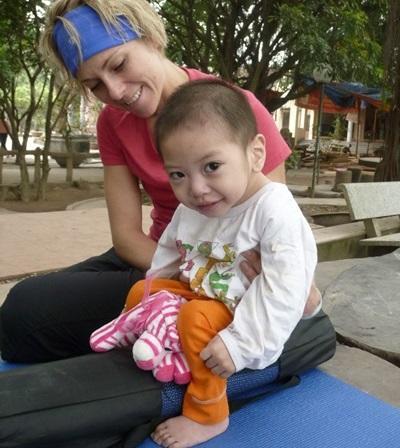 Una volontaria del progetto di terapia occupazionale assieme ad un bambino in Vietnam