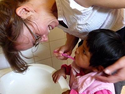 Una volontaria in missione umanitaria in Bolivia aiuta una bambina con l'igiene personale