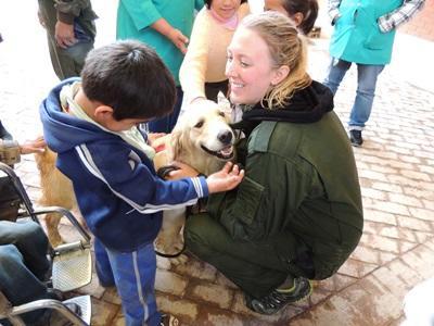 Una volontaria del progetto di terapia canina aiuta i bimbi con disabilità ad avvicinarsi ai cani in Bolivia
