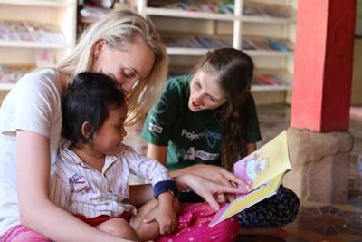 Volontarie leggono una favola ad una bambina durante una missione umanitaria in Cambogia