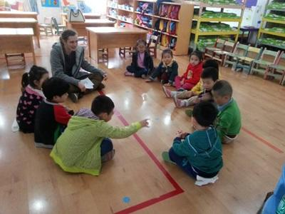 Un volontario insegna un nuovo gioco ai bambini del progetto in missioni umanitarie in Cina