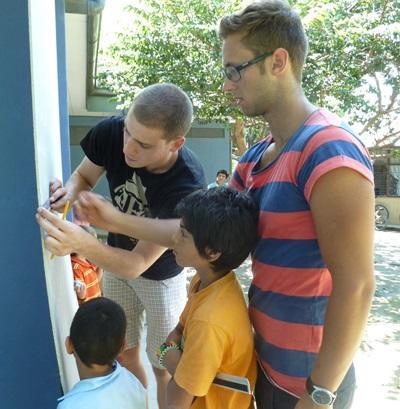 Due ragazzi del progetto di volontariato in missioni umanitarie intrattengono i bambini di una scuola