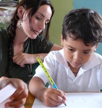 Una volontaria in missione umanitaria insegna a disegnare ad un bambino alle Galapagos