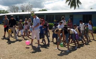 Un gruppo di volontari del progetto in missioni umanitarie gioca con i bambini alle Fiji