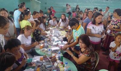 Alcuni volontari aiutano i bambini durante il pranzo in una scuola alle Filippine
