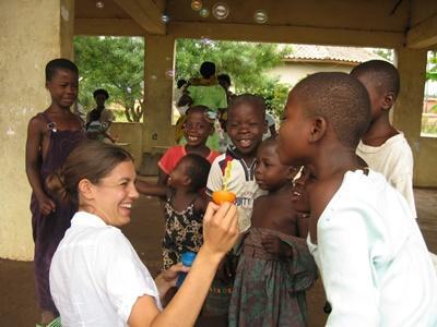 Una volontaria in missione umanitaria con un gruppo di bambini ad Accra