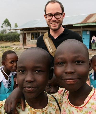 Un volontario posa per una foto con alcuni bambini duarante una missione umanitaria in Kenia