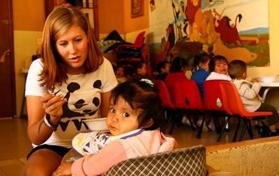 Una volontaria in missione umanitaria aiuta una bambina con il pranzo