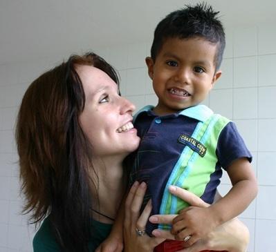 Una volontaria in missione umanitaria gioca con un bambino in Messico