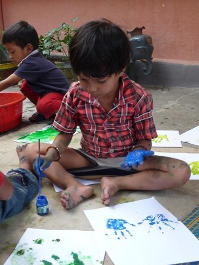 Un bambino del progetto in missioni umanitarie in nepal gioca con le tempere