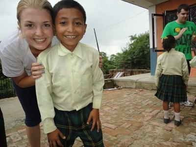 Una volontaria posa per una foto con un bambino del luogo durante una missione umanitaria in Nepal