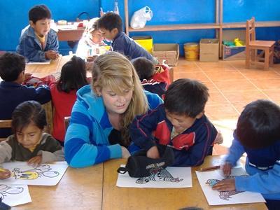 Volontaria del progetto di missioni umanitarie si prende cura di alcuni bambini in Perù