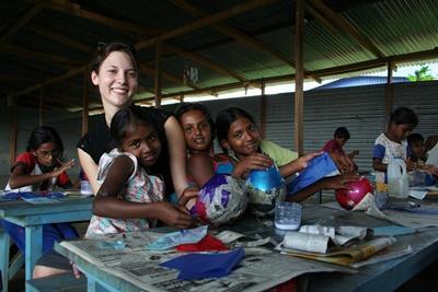 Una volontaria in missione umanitaria con un gruppo di bambini in Sri Lanka