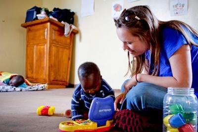 Una volontaria del progetto in missioni umanitarie accudisce un bambino a Cape Town