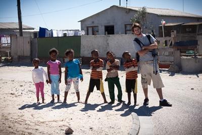 Un volontario del progetto in missioni umanitarie accudisce un gruppo di bambini in Sudafrica