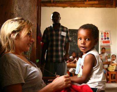 Una volontaria in missione umanitaria gioca con una bambina in Tanzania