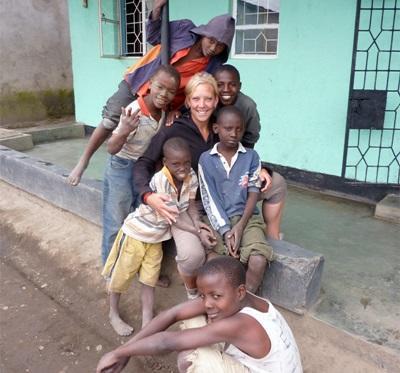 Una volontaria in missione umanitaria con un gruppo di bambini in Tanzania