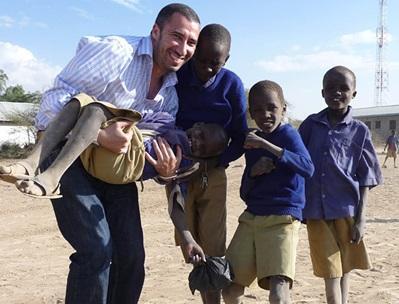 Un gruppo di bambini posa con un volontario in missione umanitaria in Tanzania