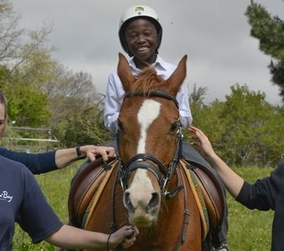 Un bambino cavalca durante una sessione di terapia equestre a Cape Town, Sudafrica