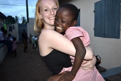 Una volontaria in missione umanitaria abbraccia una bambina a Lomé