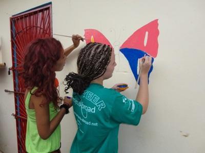 Due volontarie decorano una scuola durante un progetto di missioni umanitarie in Togo