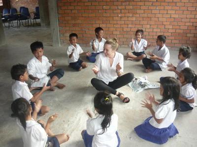 Una volontaria delle missioni umanitarie di ProjectsAbroad  gioca con i bambini in Cambogia