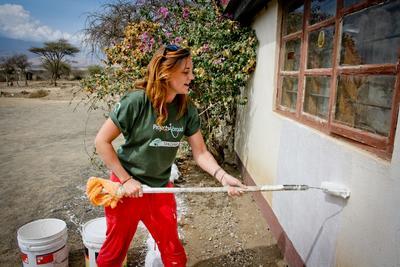 Una volontaria tinteggia il muro di una scuola in Tanzania