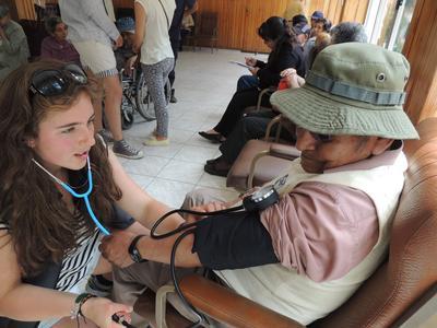 Una volontaria di medicina in Bolivia misura la pressione