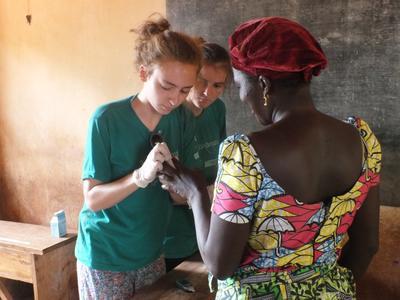 Due volontari effettuano il test della glicemia durante la visita in un villaggio del Togo