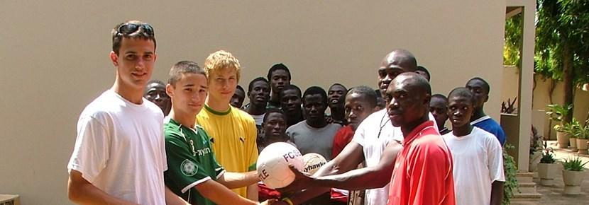 Volontari internazionali in posa con una squadra locale di calcio.