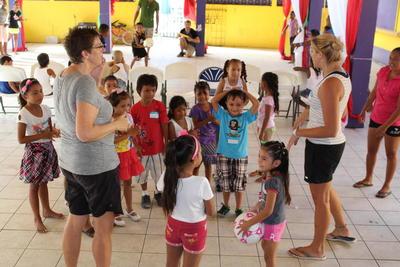 Due volontarie in Belize durante le attività di gioco con un gruppo di bambini